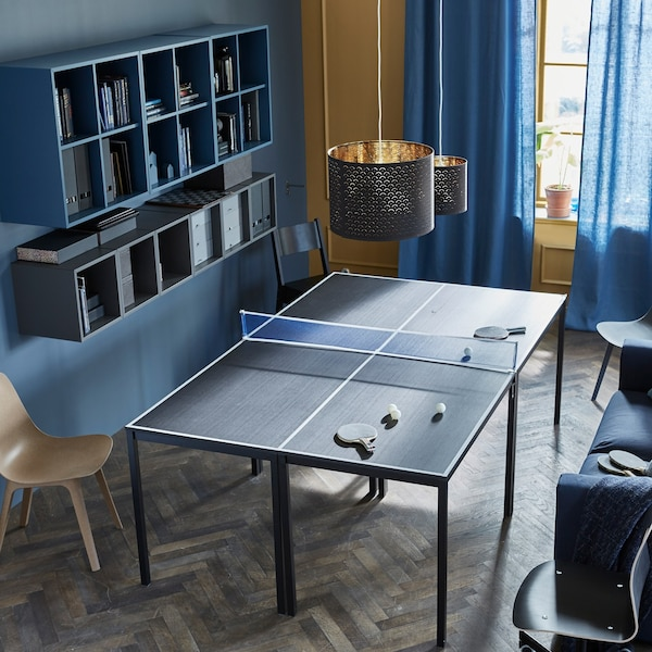 Four tables are placed together to create a ping-pong table, complete with a net and paddles.