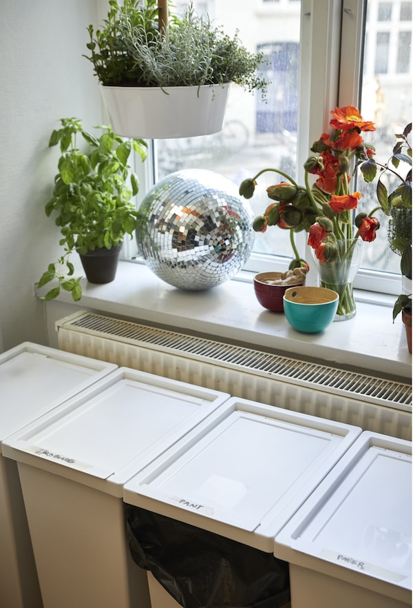 Four waste boxes below a windowsill in a kitchen.