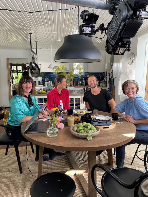 Four white people sit around a circular table in a kitchen. They wear brightly colored clothes and a large commercial video camera is visible filming them in the foreground.