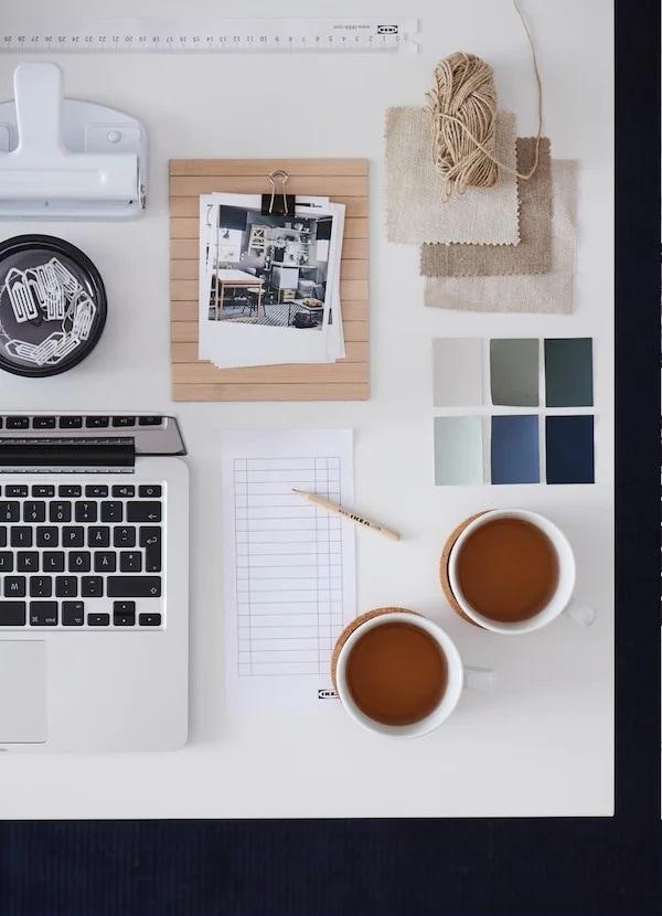 Fragment klawiatury laptopa z białą kartką papieru i ołówkiem. Obok stoją dwie filiżanki z herbatą i kilka próbek kolorów.