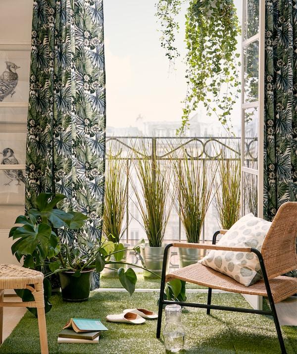 Francuski balkon i krzesło w słońcu, drzwi otwarte, otoczone wiszącymi i stojącymi roślinami, zielonymi tekstyliami i sztuczną trawą.