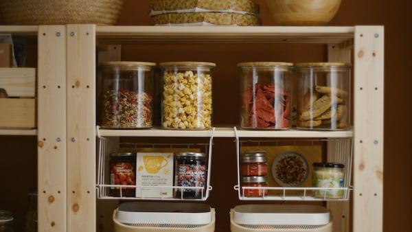 Frascos de vidro com alimentos conservados e frascos em cestos metálicos numa estante de madeira.