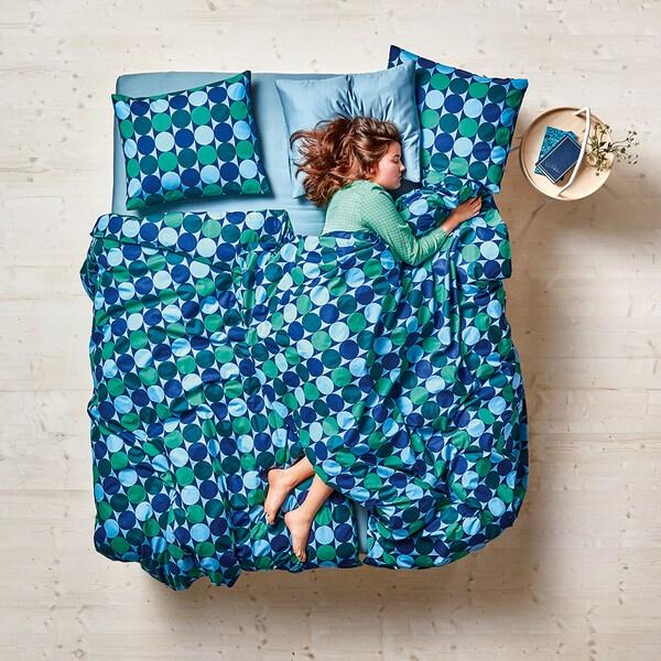Frau liegt im Bett und ist zugedeckt mit der KROKUSLILJA Bettwäsche