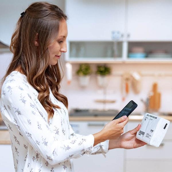 Frau scannt IKEA PRodukte im EInrichtungshaus mit Scan & Pay
