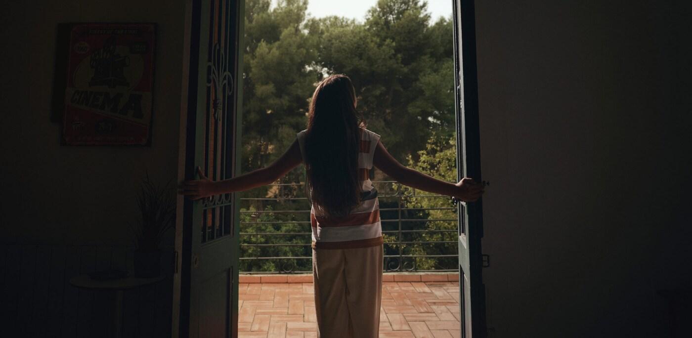 Frau schaut aus der Balkontür in die Natur, die durch den Klimawandel bedroht ist.