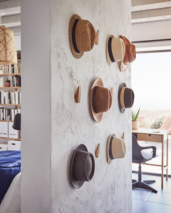 Freestanding wall with SKUGGIS hooks in bamboo that are mounted in different heights and hats are hanging on some of them.