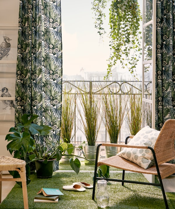 French balcony and chair in the sun, doors open, framed by hanging and standing plants, green textiles and artificial grass.