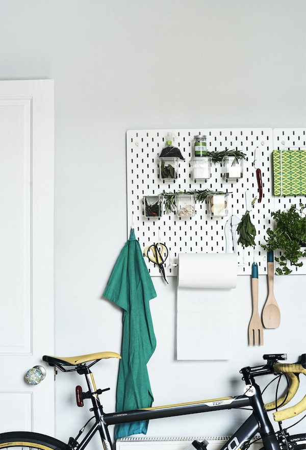 Fresh herbs and utensils stored on a pegboard.