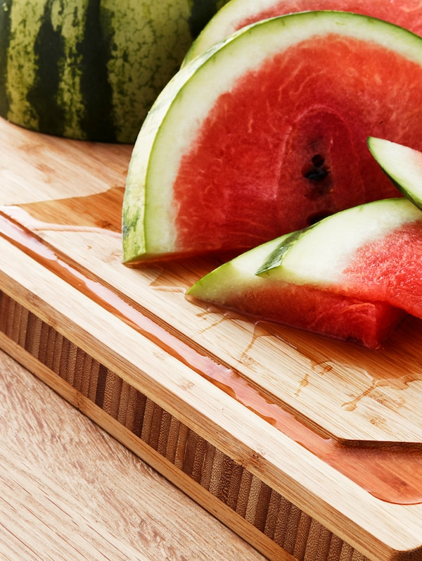 Fresh pieces of cut watermelon are lying on top of an IKEA APTITLIG bamboo butcher's block.