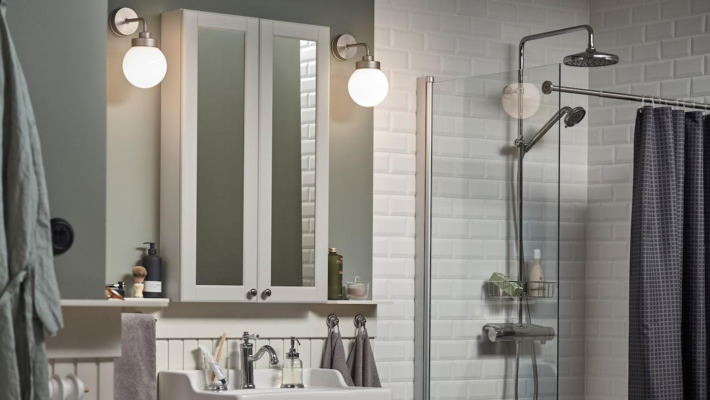 라이트그린 색상의 벽에 화이트 타일이 깔린 욕실, 양 옆에 FRIHULT 프리훌트 벽등이 달려 있는 GODMORGON 고드모르곤 거울장.