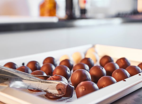 Frische Schokoladentrüffel auf einem weißen Blech, daneben TILLREDA Induktionskochfeld, tragbar weiß.