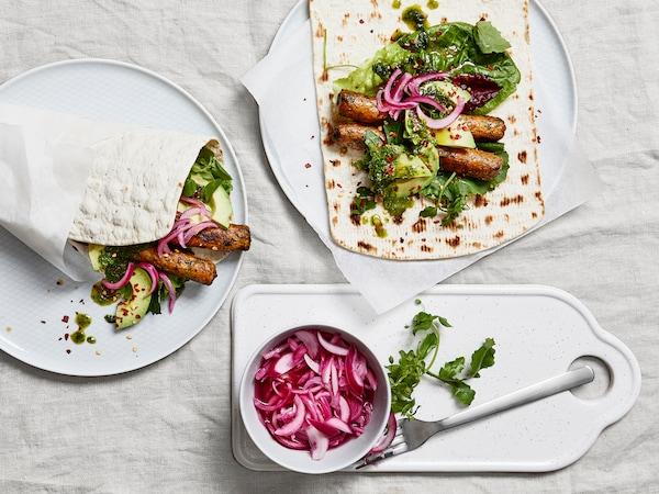 Friss zöldségek és vegán rolók tortillába tekerve tányérokon.