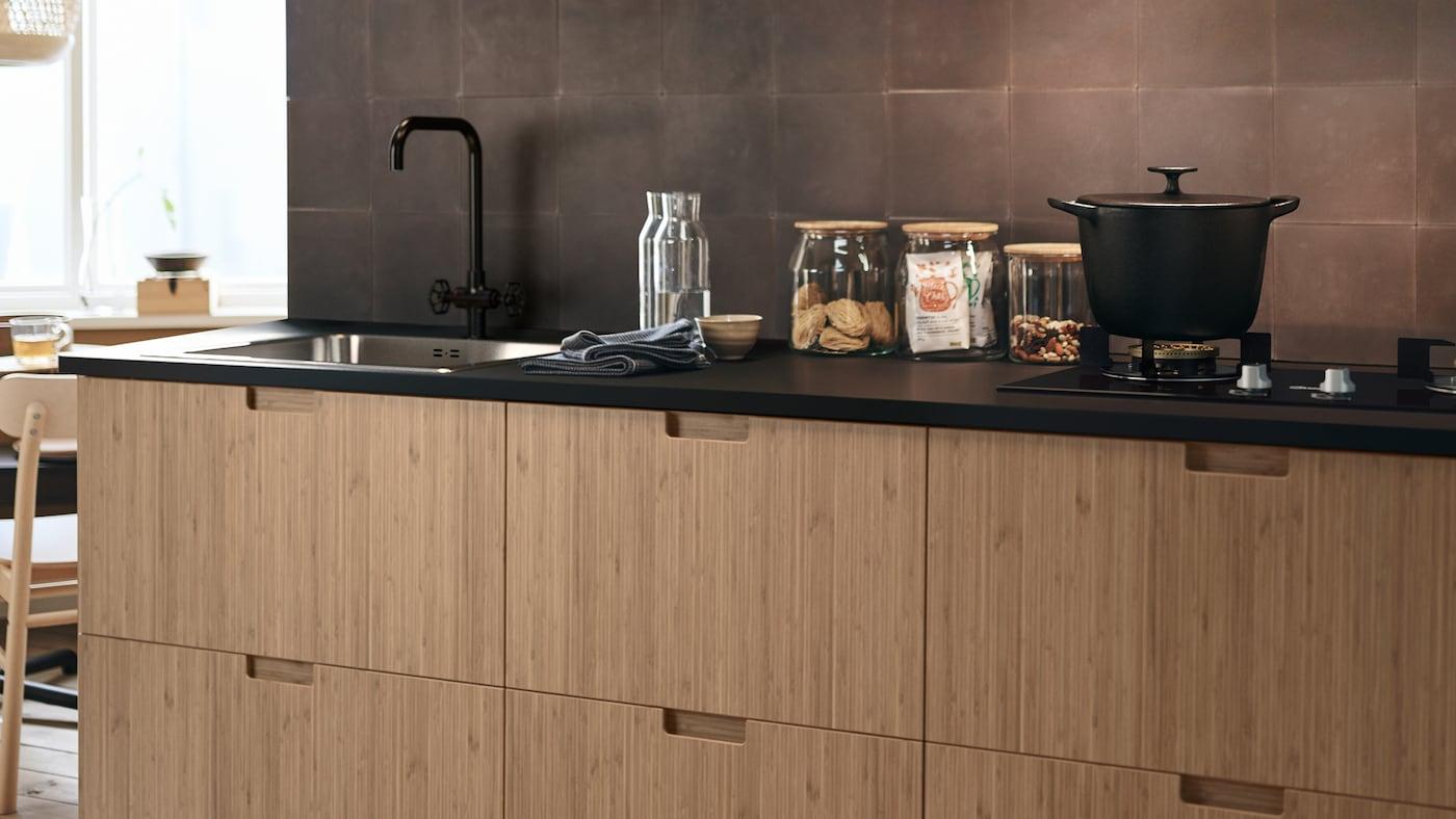 หน้าลิ้นชักครัว FRÖJERED/เฟรยเรียด ทำด้วยไม้ไผ่ และโหลแก้วแบบต่าง ๆ บนท็อปครัว และหม้อทำอาหารอยู่บนเตา