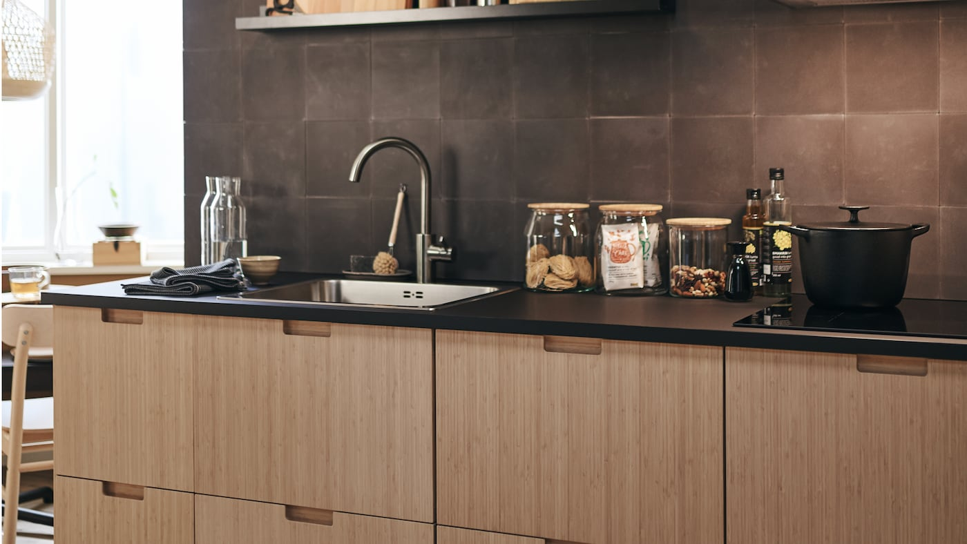 FRÖJERED kitchen fronts in bamboo, with diverse glass jars on the work surface and a cooking pot on the hob.