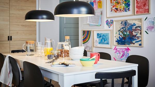 Frokost dekket på et hvitt EKDALEN bord med svarte stoler og to svarte taklamper, barnetegninger på veggen bak.