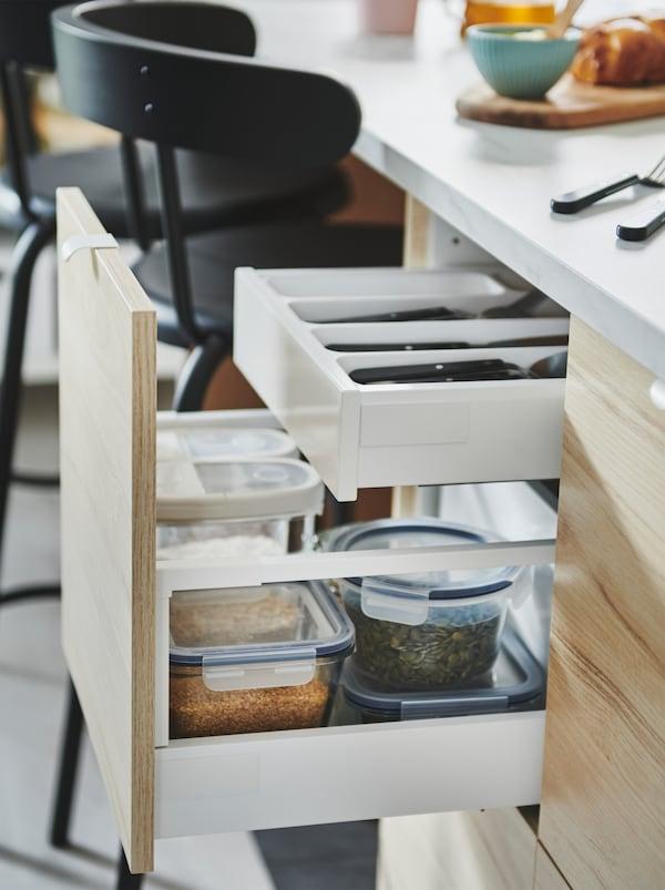 Front de sertar ASKERSUND tras în față a unei insule de bucătărie, dezvăluind o soluție de sertar pe două niveluri, atât cu tacâmuri, cât și cu recipiente alimentare.