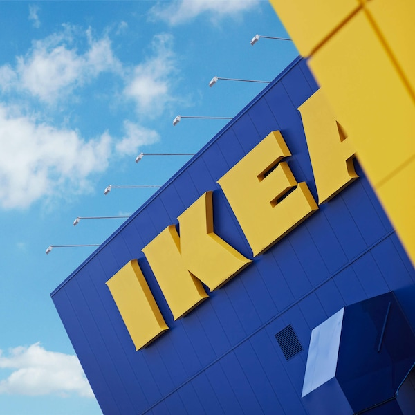 Front of an IKEA store with blue skies and white couds above.
