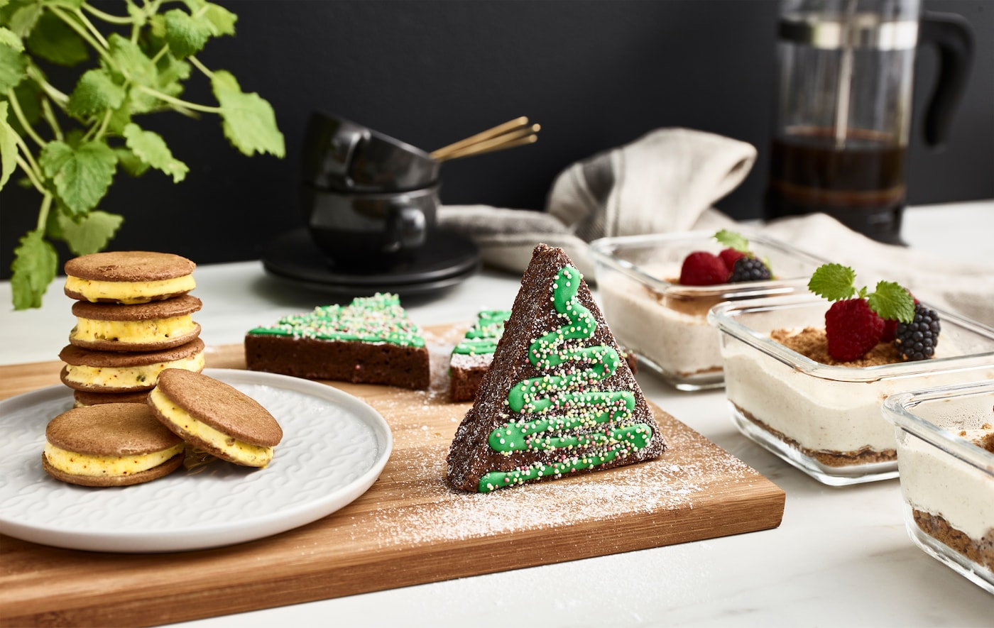 Frozen desserts, ginger snaps, festively decorated cakes, coffee cups and brewed coffee on a work top.