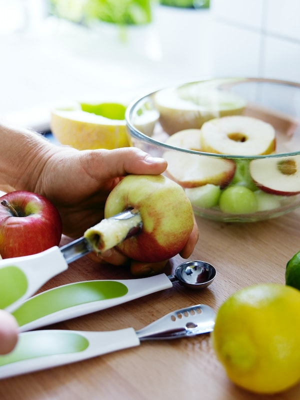 Fruits being cut with fruit garnishing set. A bowl of fruits in the background