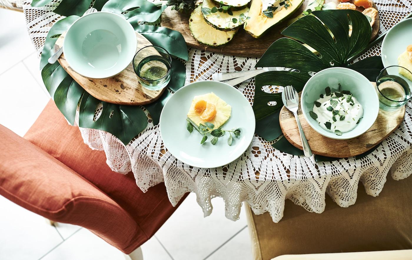 Fruits et yaourts servis sur une table décorée de grandes feuilles, de planches en bois et de vaisselle verte.
