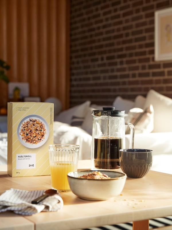 Frukost uppdukad på ett vardagsrumsbord, med bland annat ett glas juice, en kanna kaffe och HJÄLTEROLL müsli.