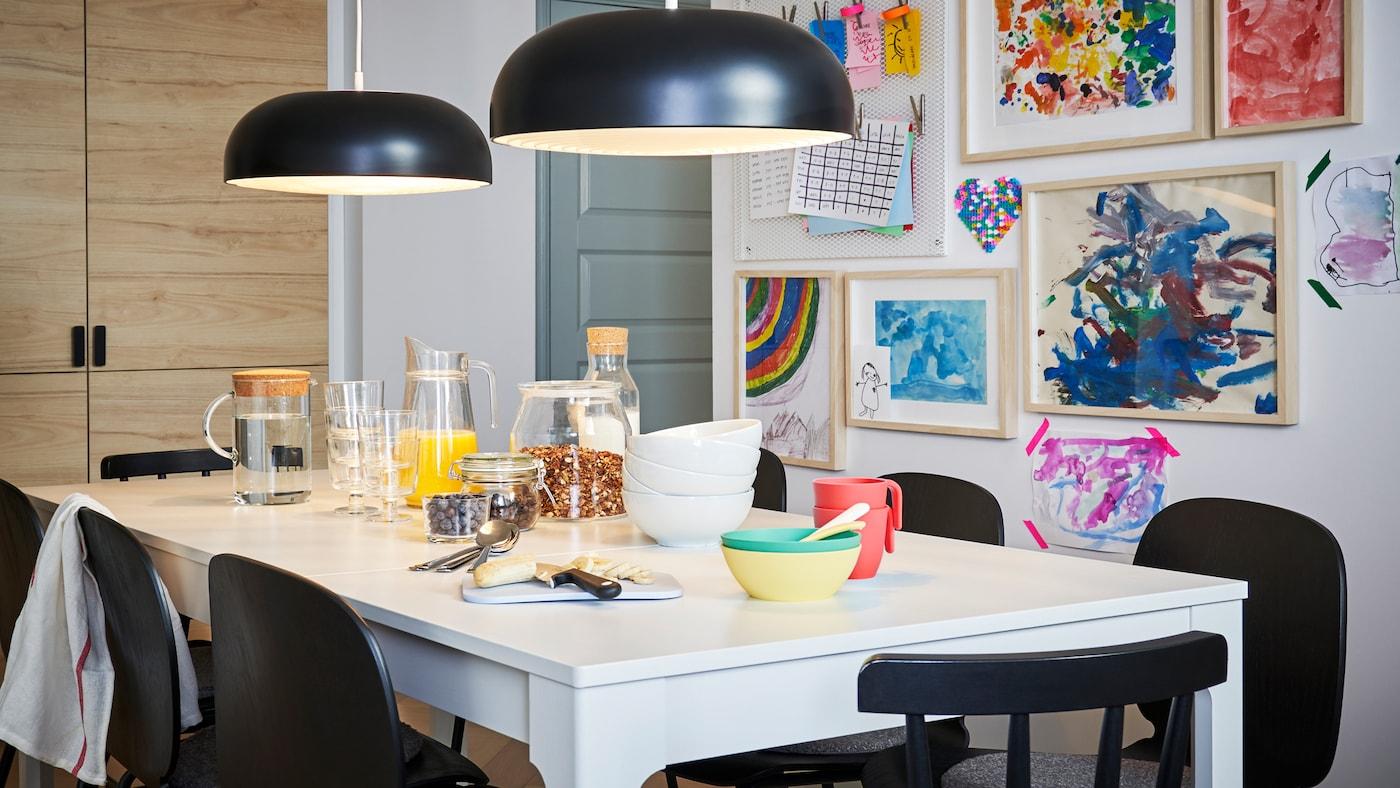 Frukost uppdukad på ett vitt EKEDALEN bord med svarta stolar och två svarta taklampor, och på väggen bakom hänger barnteckningar.