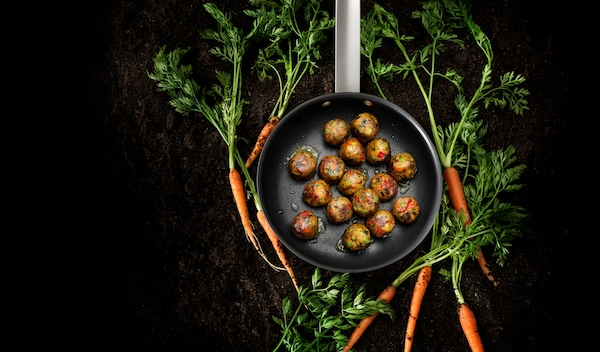 Frying pan containing vegetarian meatballs and surrounded by carrots on a black background