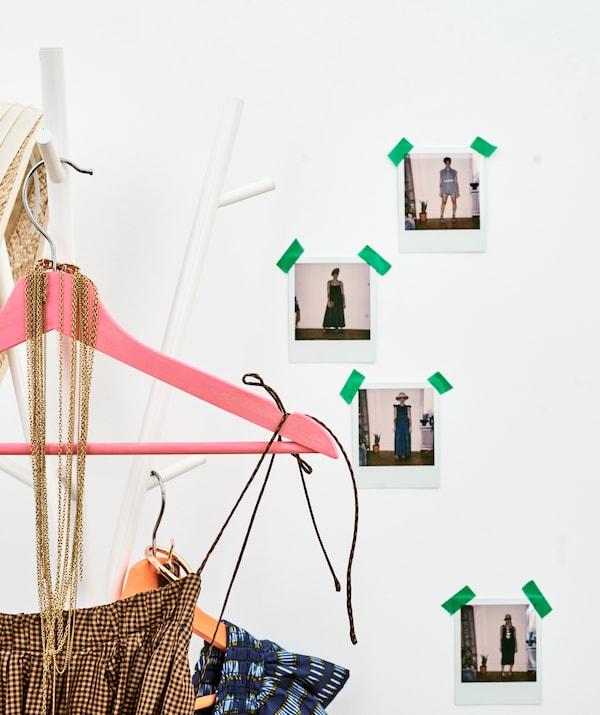 فساتين كاروهات صيفية على علاقات ملونة تتدلى على حامل معاطف بجانب حائط ملصق عليه صور امرأة بملابس مختلفة.