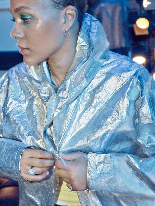فتاة بشعر قصير، وظلال عيون فيروزيوثقب في الأنفتغلق أزرارمعطف مطر فضي.