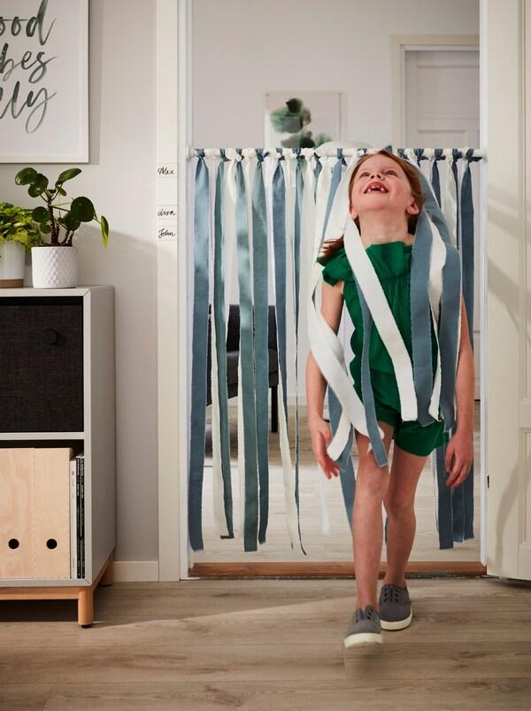 فتاة مبتسمة تمر، رأسها مائل للخلف، أسفل عمود BOTAREN مزين بأشرطة قماش DITTE ومعلقة عبر مدخل.