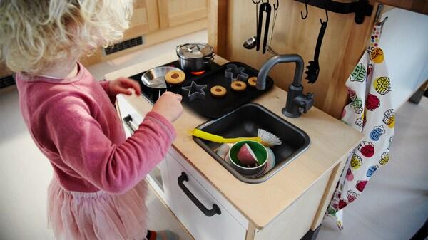 فتاة صغيرة تتظاهر بخبز البسكويت في مطبخها اللعبة، دلالة على أن سلامة الأطفال أولوية لدى ايكيا.