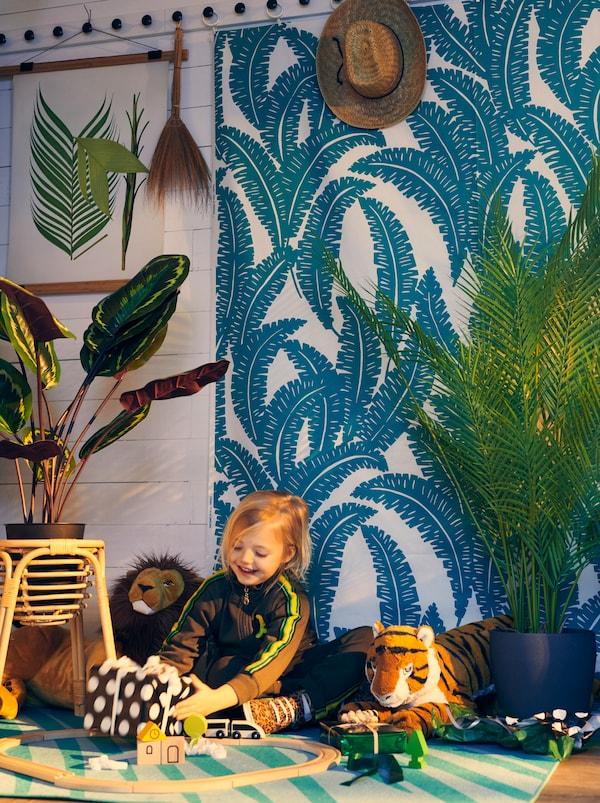 فتاة تحمل هدية ملفوفة في غرفة بها نباتات، وقماش UGGLEMOTT على الحائط وسجادة GRACIÖS، تضفي على الغرفة طابع الغابة.