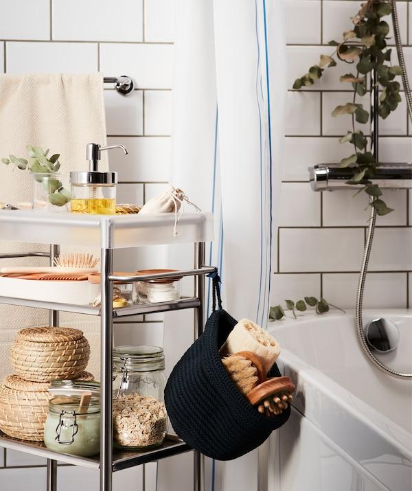 Fürdő stílusú kiegészítőkkel töltött zsúrkocsi egy fürdőkád mellett; eukaliptusz ág lóg a zuhanyfejről.