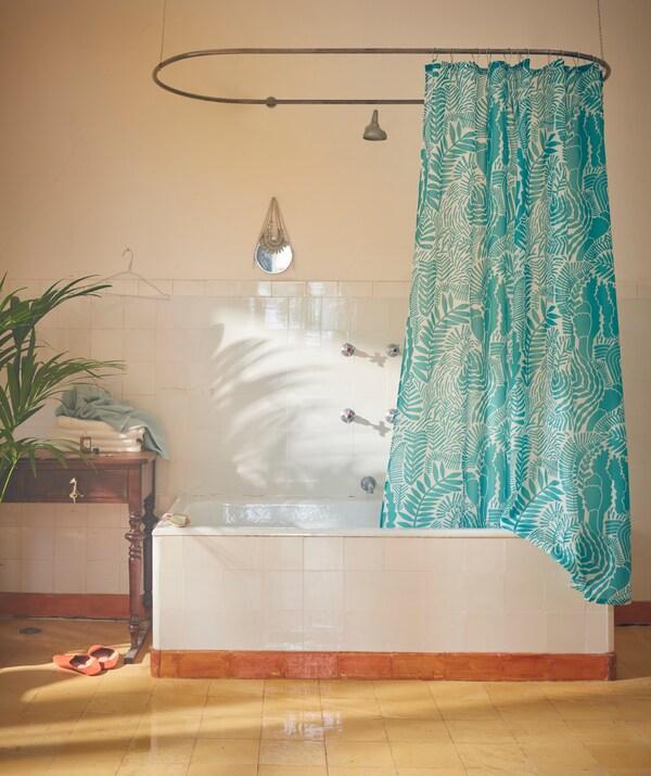 Fürdőszobabelső: GATKAMOMILL zuhanyfüggöny lóg egy rúdon, elliptikus formát alkotva.