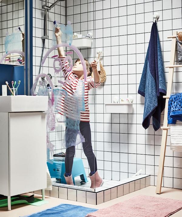 Fuldt påklædt barn med gummistøvler, som står i en brusekabine og maler med vandfarver på en brusevæg af glas.