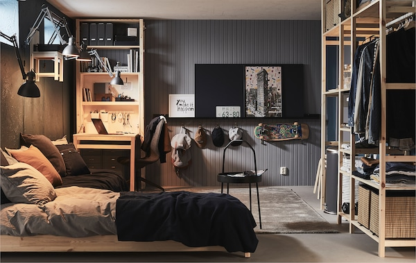 Fully furnished room with high windows, as in a basement or garage, with bed, desk and storage in various shelving units.