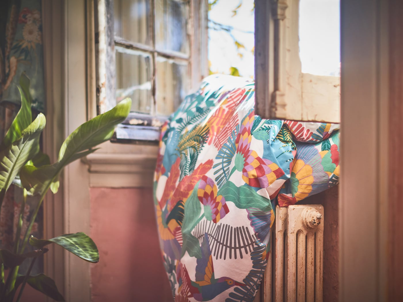 Funda nórdica SKOGSFIBBLA con un colorido estampado aclarado por el sol, colocada en una antigua ventana abierta sobre un radiador.