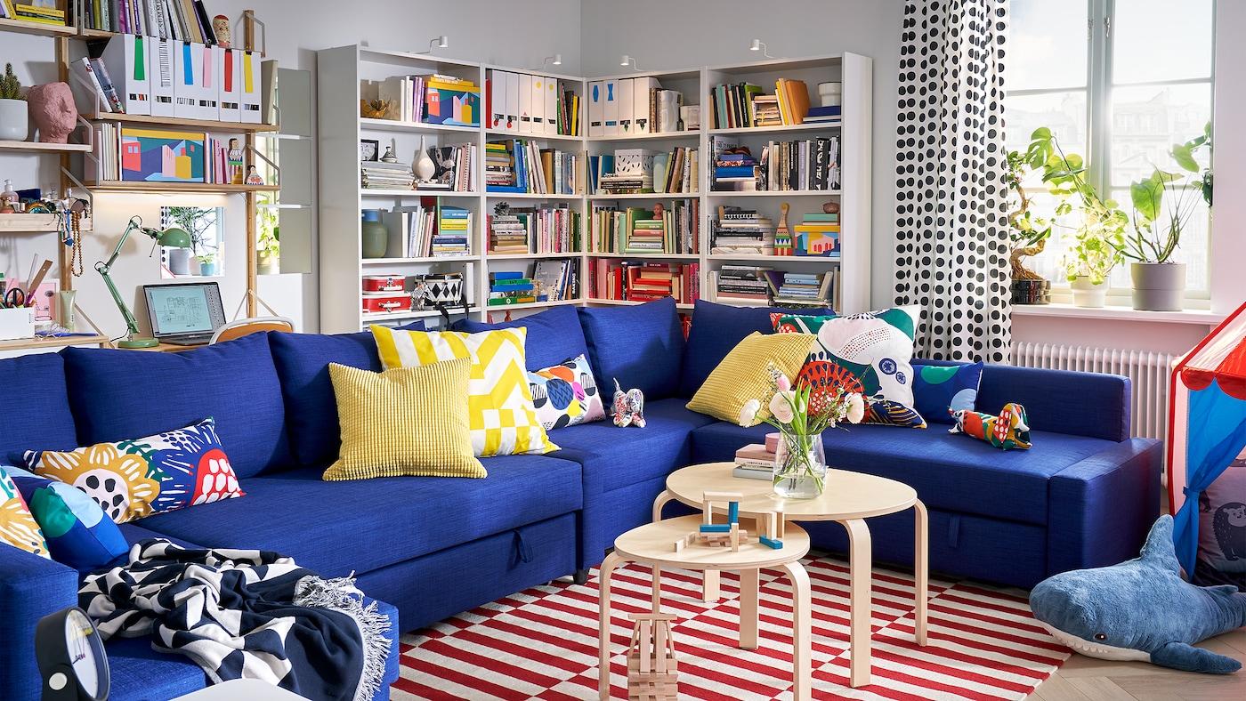 Funktionelles Wohnzimmer mit dem blauen FRIHETEN Eckbettsofa und vielen Kissen, Bücherregalen und einem Fenster mit Pflanzen auf der Fensterbank.