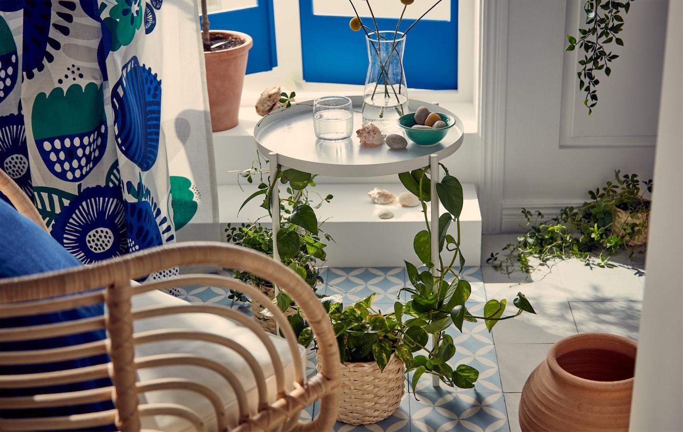 フレンチバルコニー風の窓のすぐそばの日当たりの良い場所にあるブルーとホワイトのインテリア。植物を巻きつけたトレイテーブルのそばの藤のアームチェア。