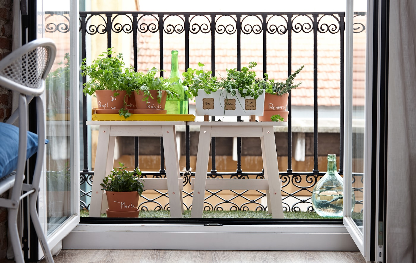 Furnish a tiny balcony with plants to extend living space.