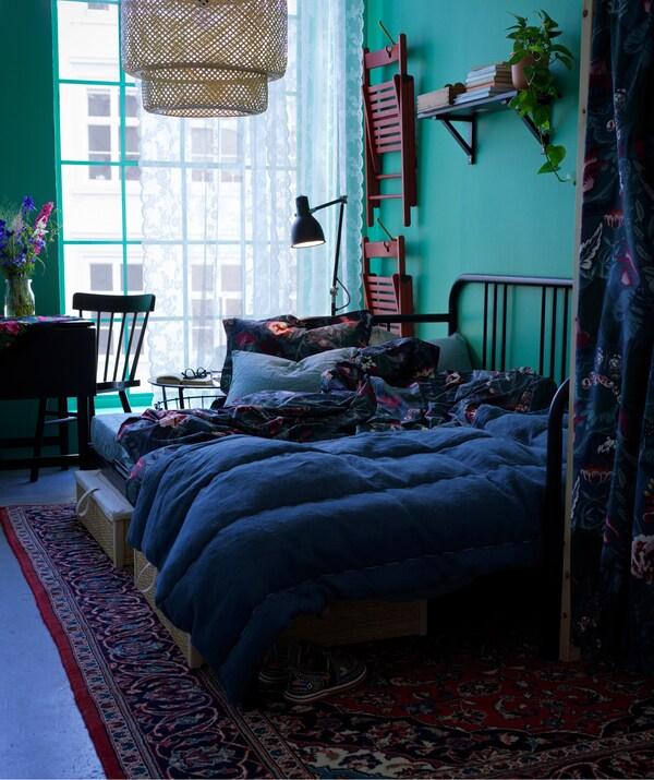 FYRESDAL Tagesbett mit Blumenbettwäsche vor einer grünen Wand in einem Wohnraum