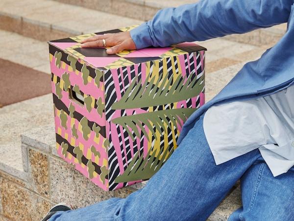 Fyrkantig OMBYTE flyttkartong med rosa och gröna mönster inspirerade av växter och vilda djur.