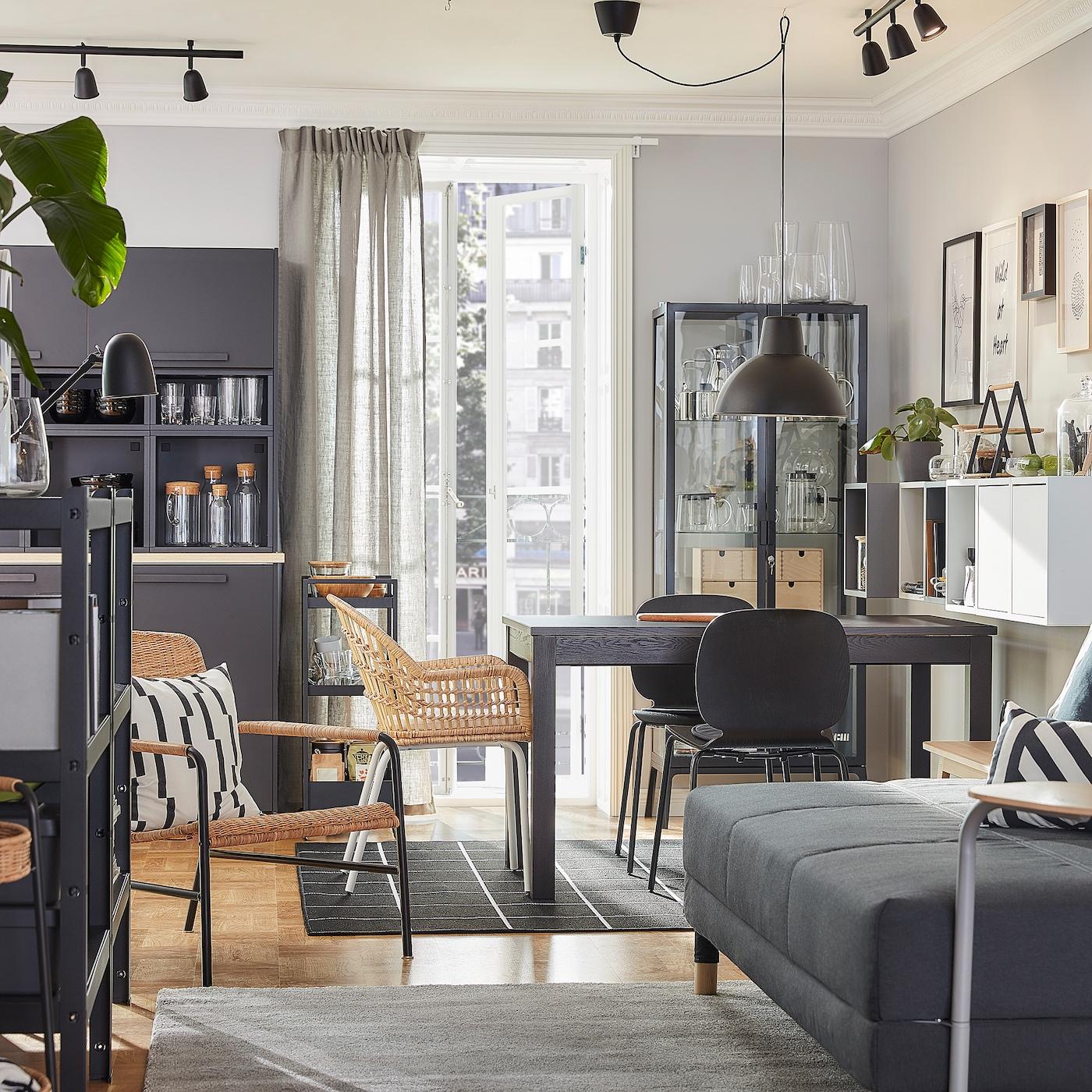 Gabungan ruang tamu dan ruang makan yang diselaraskan gayanya dengan perabot rotan dan warna coklat, kelabu dan antrasit.