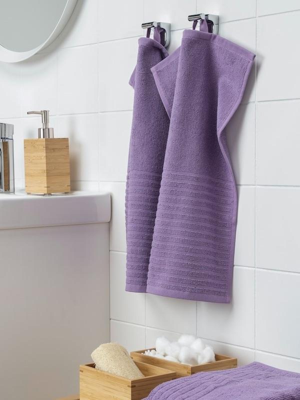 Gästehandtuch lila im Sale hängt an einer weißen Badezimmerwand.