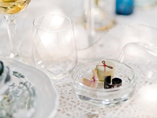 Gästgåva i form av en glasburk med en liten parlin och en rullad papperslapp med ett meddelande står vid varje kuvert runt middagsbordet.