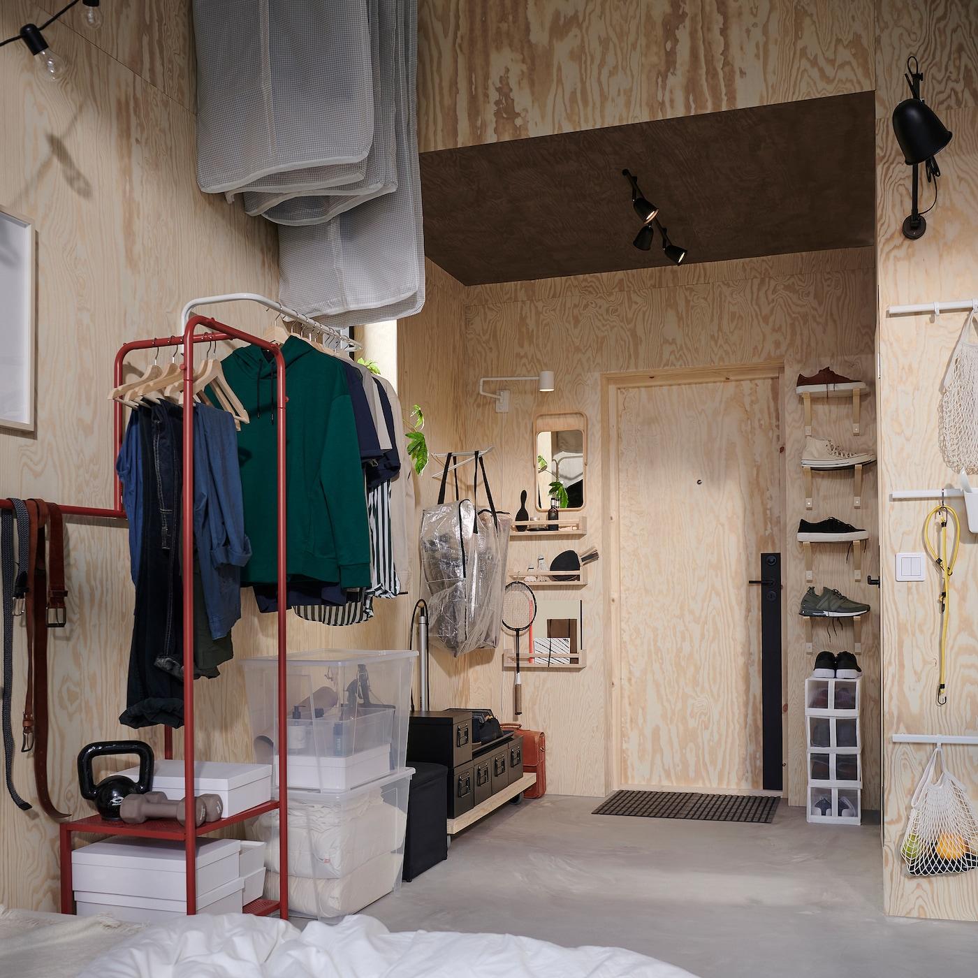 天井が高くて狭い玄関。ハンガーレールとブラケットを縦に並べて取り付け、衣服やシューズの収納場所にしています。