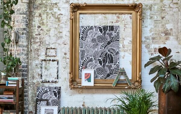 Galeri fabrik bercorak yang dibingkaikan dipamerkan di dinding batu bata dengan bingkai besar berwarna keemasan, tumbuh-tumbuhan gantung dan rak buku rendah.