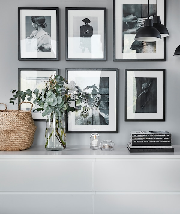 Galerie d'art improvisée, photos noir et blanc sur un mur, au-dessus de deux commodes blanches.