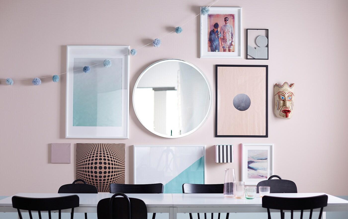 Galerie murale avec cadres de différentes tailles, miroir et objets personnels.