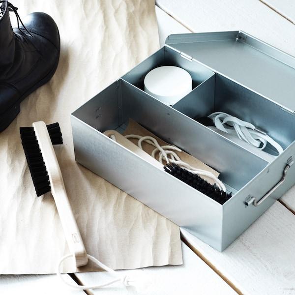 Galvanisierte Box mit schuhputzmitteln und Zubehör neben einer Schuhputzbürste.